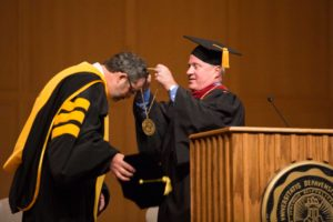 Chair of the DePauw University Board of Trustees, Marshall Reavis '84, endows President Mark McCoy with the presidential medallion during the inauguration saturday.   SAM CARAVANA / THE DEPAUW